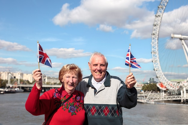 Senior paar hält britische flagge in london mit millenium rad