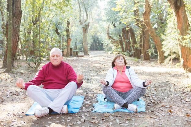 Senior paar mit gekreuzten beinen während der meditation