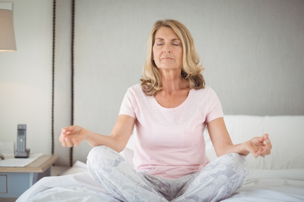 Senior praktiziert yoga auf dem bett