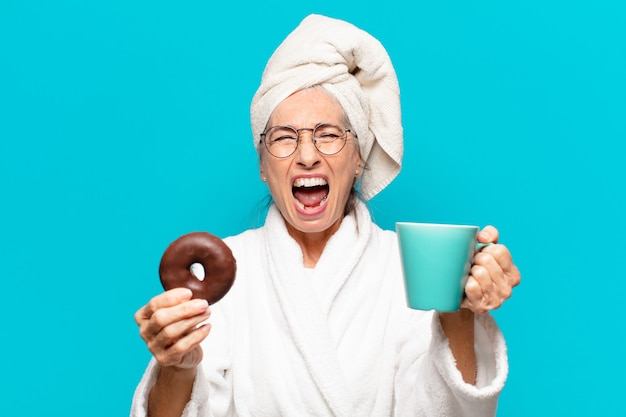 Senior pre-frau nach der dusche und bademantel und frühstück mit kaffee und donut breakfast