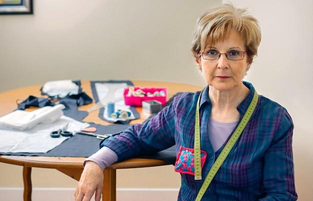 Senior schneiderin posiert mit blick in die kamera mit tisch mit nähmaterialien im hintergrund