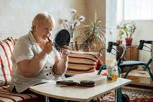 Senior schönheit und hautpflege senioren plus größe blonde frau mit behinderung auftragen von lippenstift