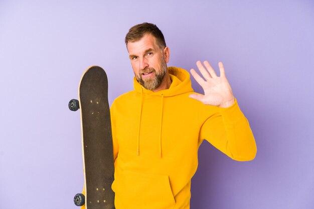Senior skater mann isoliert auf lila wand lächelnd fröhlich zeigt nummer fünf mit den fingern.