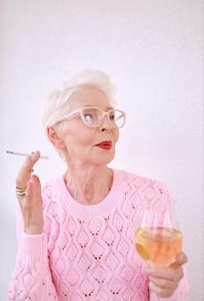 Senior stilvolle frau raucht zigarette mit glas weißwein