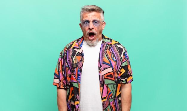 Senior traveller tourist, der sehr schockiert oder überrascht aussieht und mit offenem mund starrt und wow sagt