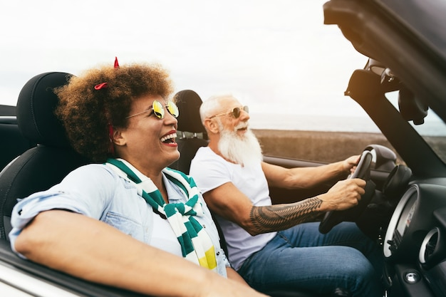 Senior trendiges paar in einem cabrio auto in der urlaubszeit - reise, mode und freudiges älteres konzept - fokus auf frauengesicht