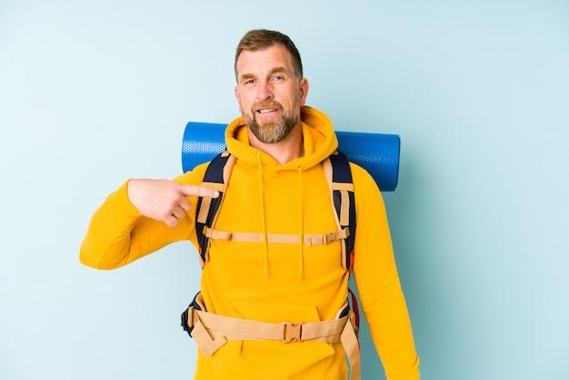 Senior wanderer mann isoliert auf blaue person, die von hand auf einen hemdkopierraum zeigt, stolz und zuversichtlich