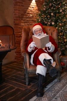 Senior weihnachtsmann in brille sitzt in ledersessel am kamin und liest buch im wohnzimmer...