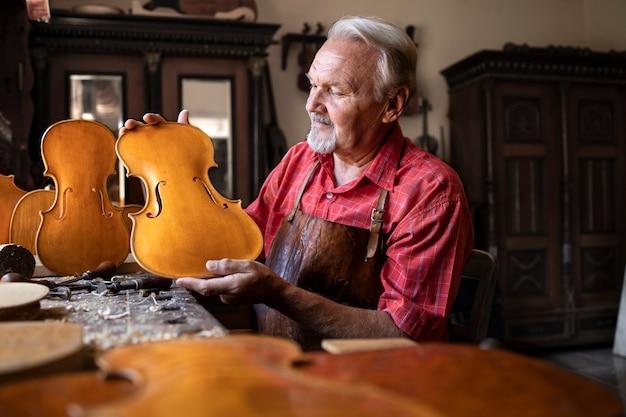 Senior zimmermann, der geigenmusikinstrument baut