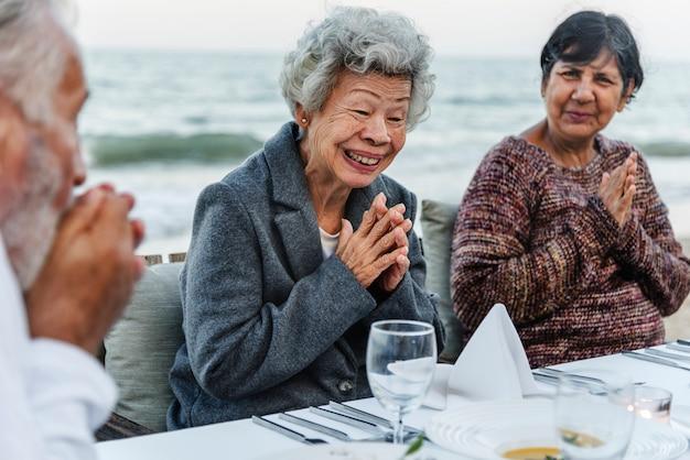 Senioren, die ein abendessen am strand haben