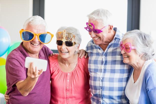 Senioren, die ein selfie mit lustigen gläsern nehmen