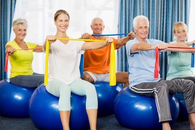 Senioren, die gymnastikball verwenden und bänder ausdehnen