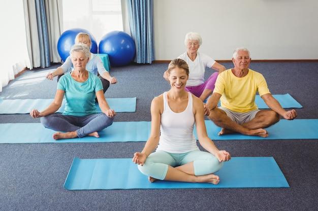 Senioren, die in lotussitz sich entspannen