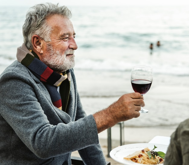 Senioren, die mit rotwein am strand rösten