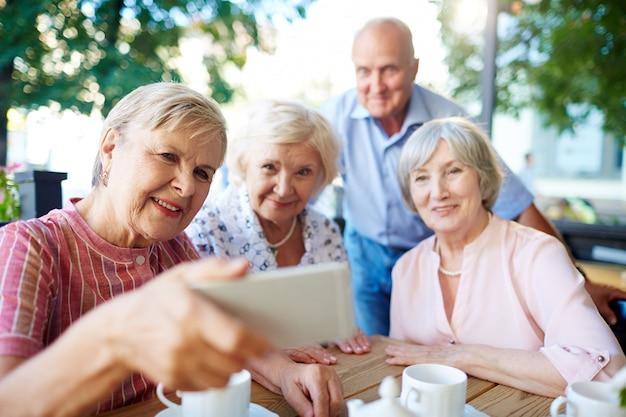 Senioren, die selfie mit smartphone nehmen