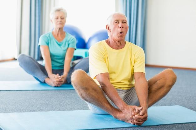 Senioren, die yoga durchführen