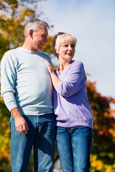 Senioren im herbst oder herbst gehen hand in hand