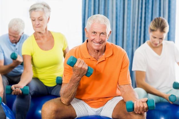 Senioren mit gymnastikball und gewichten