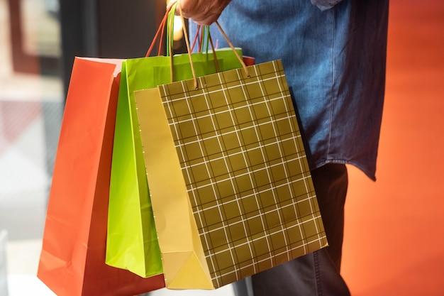 Senioren mit jeanshemd genießen den abendlichen einkauf und profitieren von angeboten und rabatten. auf seinem arm viele einkaufstüten