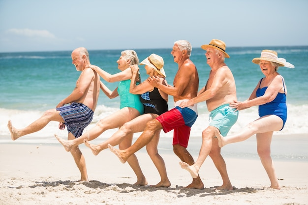 Senioren tanzen in einer reihe am strand