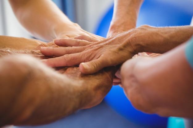 Senioren und fitnesstrainer, die ihre hände zusammenfügen