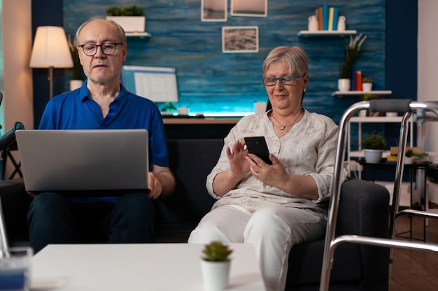 Seniorenfamilie mit modernen technologischen geräten