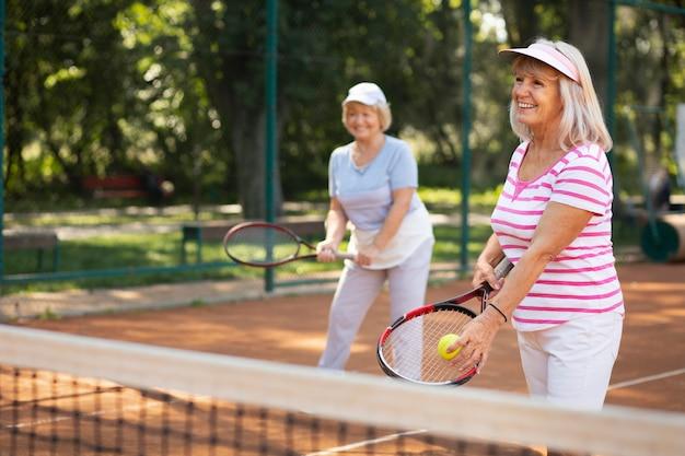 Seniorenfreunde mit mittlerem schuss, die tennis spielen