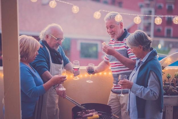 Seniorengruppe bei freizeitaktivitäten beim grillen auf der dachterrasse zu hause mit bergblick. essen und wein für zwei männer und zwei frauen, die zusammen spaß haben unter der sonne in va