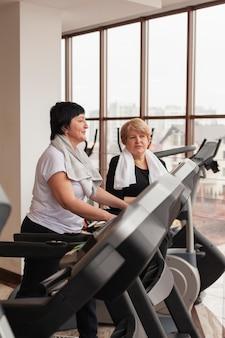 Seniorenpaar der seitenansicht im fitnessstudio