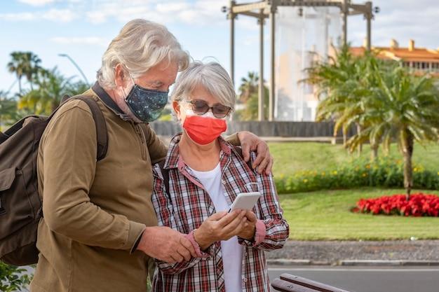 Seniorenpaar mit weißem haar und rucksacktouristen schaut sich während der stadtrundfahrt handys an und trägt aufgrund des coronavirus eine chirurgische maske. aktive rentner, die reisen und freiheit genießen