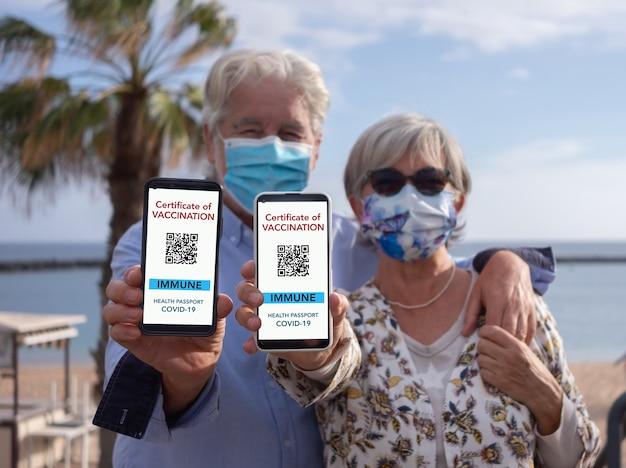 Seniorenpaar zeigt eine digitale gesundheitspass-app für menschen, die gegen coronavirus geimpft sind und urlaub am meer genießen