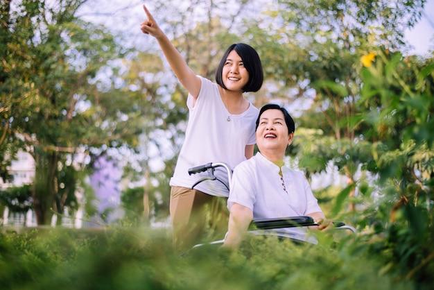 Seniorenpflegeversicherungskonzept, pflegekraft kümmern sich um ältere asiatische frau, die auf rollstuhl an der natur sitzt