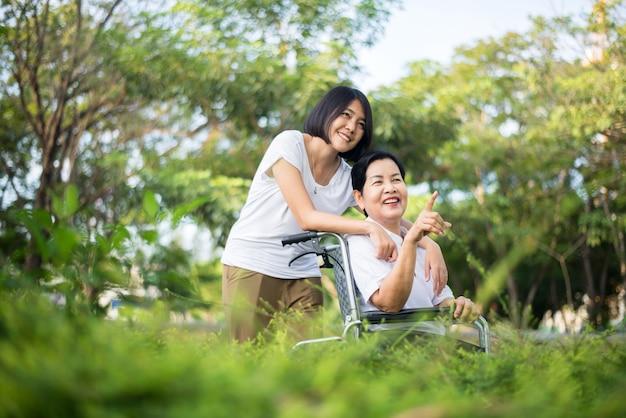 Seniorenpflegeversicherungskonzept, pflegekraft kümmern sich um ältere asiatische frau, die auf rollstuhl im freien sitzt