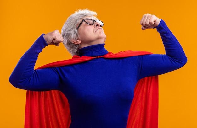Seniorin superheldin mit brille mit rotem umhang posiert vor der kamera und hebt fäuste wie ein gewinner, der kraft und stärke zeigt