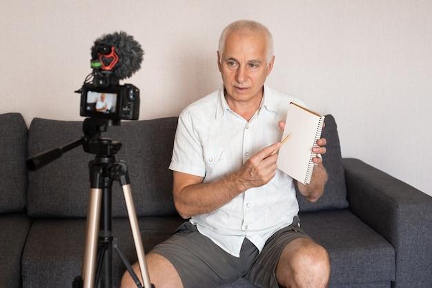 Seniorprofessor, der mit einer videokamera ein video für eine vorlesung zu hause macht
