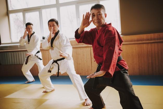 Sensei zeigt, dass taekwondo im fitnessstudio steht