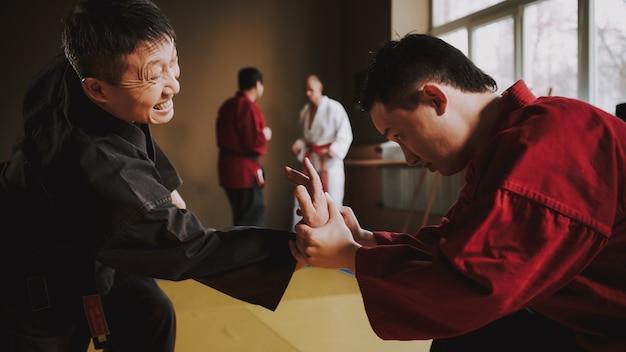 Sensei zeigt dem schüler, wie er seinen arm ringt.
