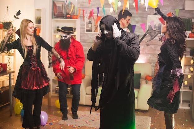 Sensenmann, der bei halloween-feier am telefon spricht. laute musik.