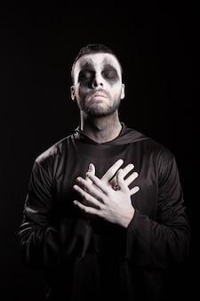 Sensenmann, der die hände auf der brust über schwarzem hintergrund hält. halloween-outfit.