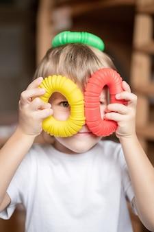 Sensorisches anti-stress-kunststoffspielzeug in kinderhänden. ein kleiner glücklicher kinderjunge spielt zu hause mit einem poptube-zappelspielzeug. kinder, die pop-tube-bunte farben halten und spielen, trend 2021-jahr