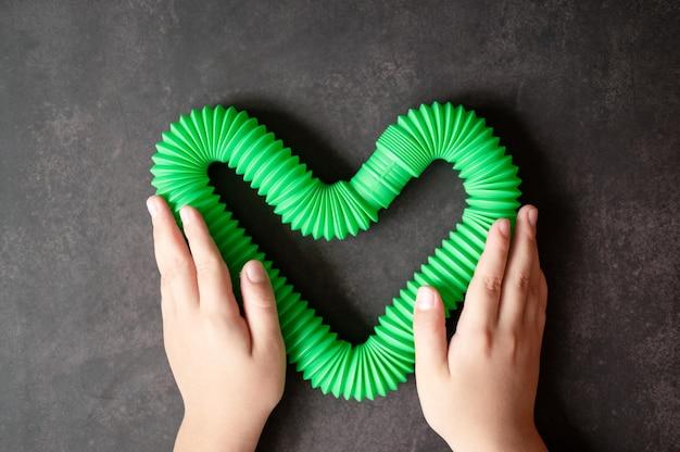 Sensorisches anti-stress-pop-tube-spielzeug in kinderhänden. ein kleines glückliches kind spielt mit einem poptube-spielzeug auf einem schwarzen tisch. kleinkinder, die pop-röhren halten und spielen, grüne helle farbe, trend 2021-jahr