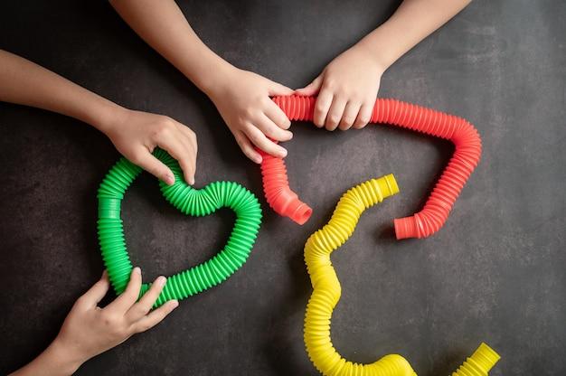 Sensorisches anti-stress-pop-tube-spielzeug in kinderhänden. ein kleines glückliches kind spielt mit einem poptube-spielzeug auf einem schwarzen tisch. kleinkinder, die pop-röhren halten und spielen, mehrfarbige helle farbe, trend 2021-jahr