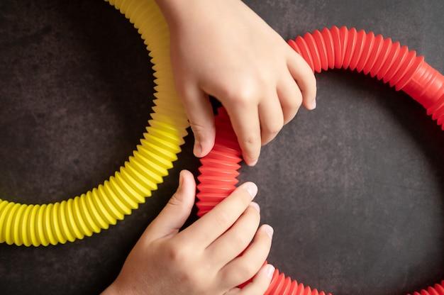 Sensorisches anti-stress-pop-tube-spielzeug in kinderhänden. kleine glückliche kinder spielen mit einem poptube-spielzeug auf einem schwarzen tisch. kleinkinder, die pop-röhren in roter und gelber heller farbe halten und spielen, trend 2021-jahr