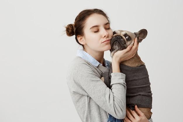 Sentimentale frau, die ihre wange drückt, um französische bulldogge, die über weißer wand isoliert wird. weibliche haustierbesitzerin, die sorgfalt und liebe ausdrückt, die ihren stammbaumhund beim gehen im park umarmt. speicherplatz kopieren
