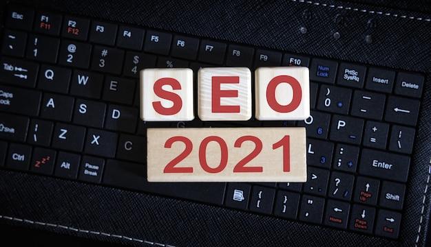 Seo 2021 konzept. holzwürfel auf einer schwarzen tastatur.