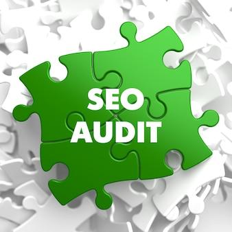 Seo audit auf grünem puzzle auf weißem hintergrund.
