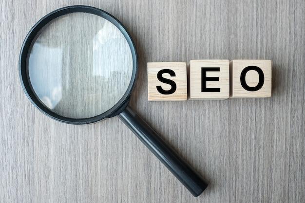 Seo (search engine optimization) text hölzerne würfel und vergrößerung