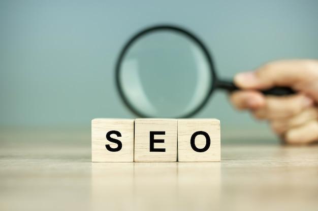 Seo (search engine optimization) text holzwürfel und lupe auf holztisch. idee, vision, strategie, analyse, keyword- und inhaltskonzept