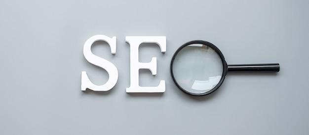 Seo (search engine optimization) text und lupe auf grau. idee, vision, strategie, analyse, keyword- und inhaltskonzept