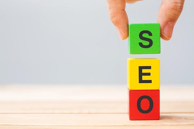 Seo (suchmaschinenoptimierung) text holzwürfelblöcke auf tabellenhintergrund. idee, strategie, marketing, keyword- und content-konzept